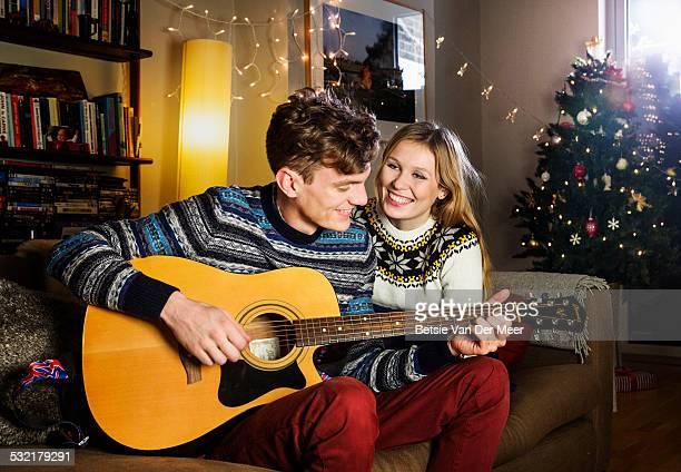 Man serenades girlsfriend with guitar at Christmas