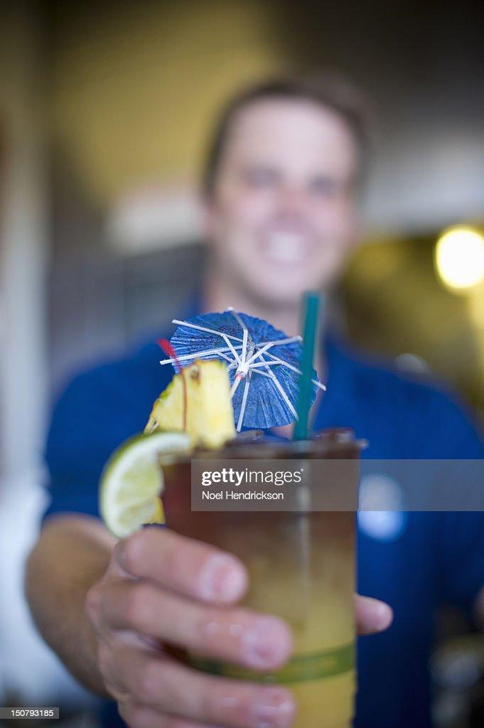 A man serves a tropical drink : Stock Photo