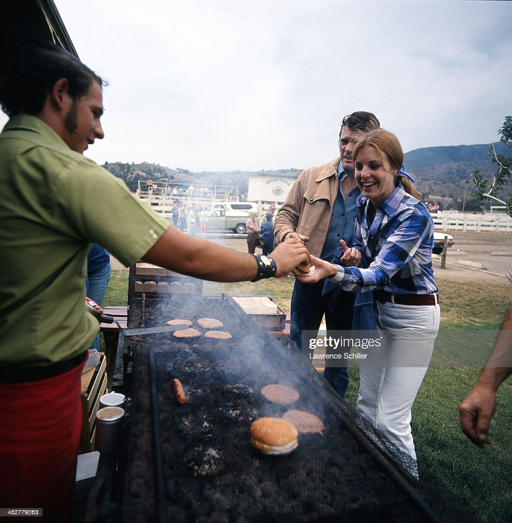 A man serves a woman a hamburger straight of the grill at an outdoor event at La Costa Country Club San Diego California 1967