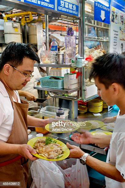 A man serves some chicken on rice from his stall at the Marvell Foodcourt