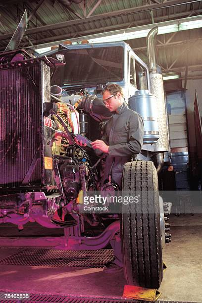 Man servicing engine of semi truck