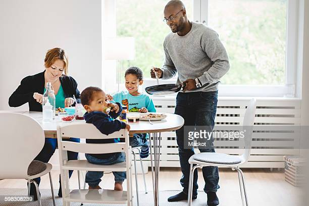 Man serving food to family at dining table in house