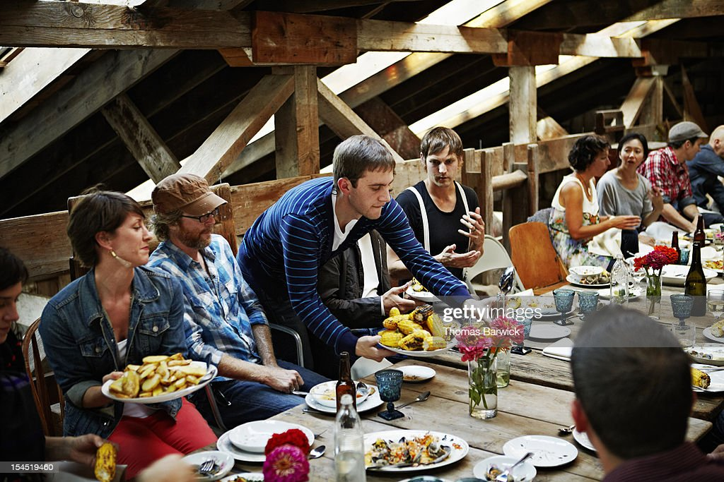Man serving food to group of friends and family : Stock Photo
