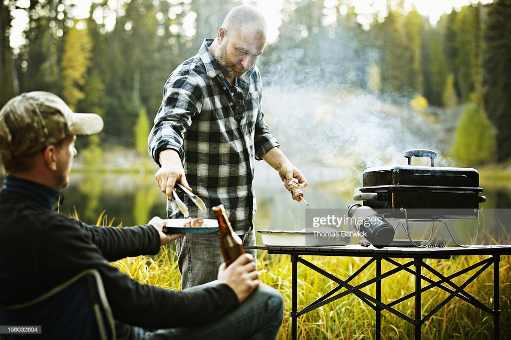 Man serving friend from outdoor barbecue : Stock Photo