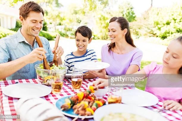 Uomo che serve Insalata di famiglia al tavolo da pranzo