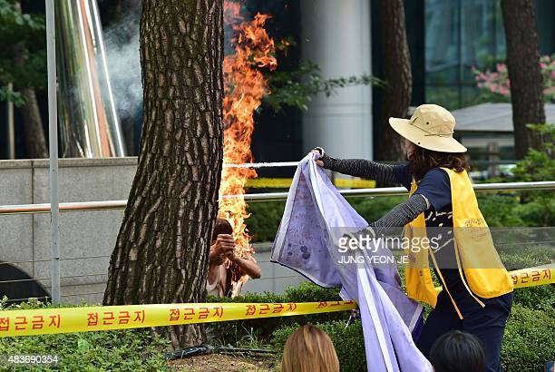 A man sets himself on fire as a South Korean woman tries to extinguish the fire outside the Japanese embassy in Seoul on August 12 2015 during a...