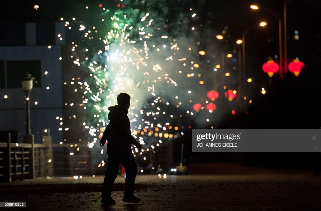 A man sets off fireworks to celebrate the Lunar New Year near the Yalu River in the Chinese border town of Dandong opposite the North Korean town of Sinuiju on February 7, 2016. North Korea said on February 7 it had successfully put a satellite into orbit, with a rocket launch widely condemned as a ballistic missile test for a weapons delivery system to strike the US mainland. AFP PHOTO / JOHANNES EISELE / AFP / JOHANNES EISELE