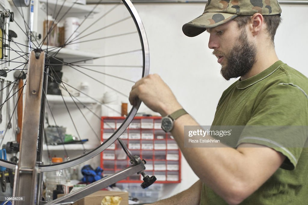 Man sets spokes in bicycle wheel : Stock Photo