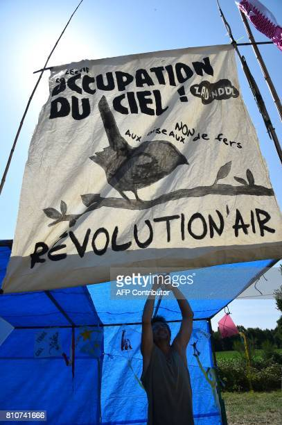 A man sets up a banner reading 'Occupation of the sky Revolution'air' during a twoday meeting organised by opponents to a controversial international...