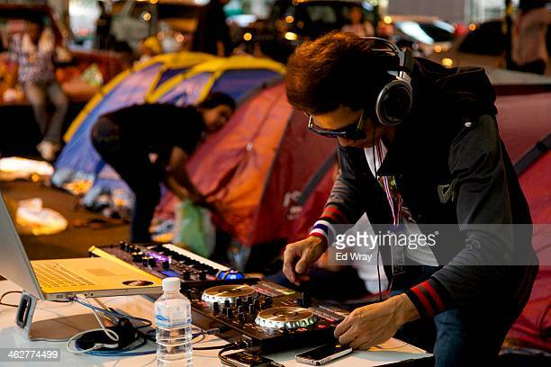 A man sets up a DJ booth next to a row of tents at one of the rally sites erected at major junctions around the city on January 15 2014 in Bangkok...