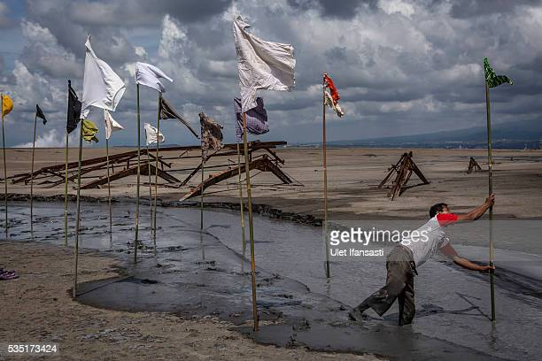A man sets up an art installation by artist Dadang Christanto with title 'Gombal' known as rags at mudflow during the tenth anniversary of the...