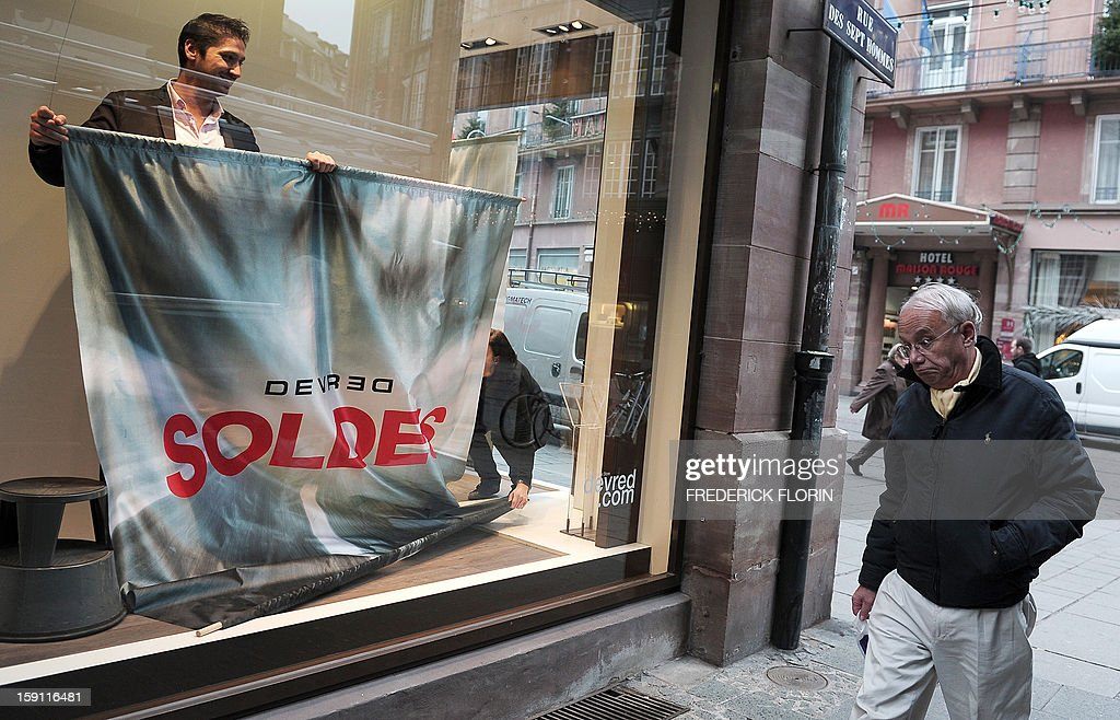A man sets up his window shop with an advertising banner announcing the winter sales on the eve of its official opening in France on January 8, 2013 in Strasbourg, eastern France. AFP PHOTO/FREDERICK FLORIN