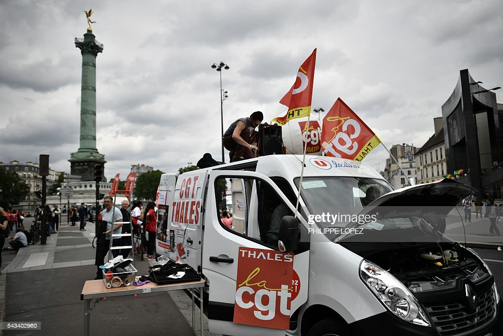 A man sets up speakers on the roof of a vehicle bearing flags of French union CGT during a demonstration against controversial labour reforms, on June 28, 2016 on Bastille Square in Paris. Unions have called repeated strikes and marches in opposition to the law, which seeks to bring down France's intractable 10-percent unemployment rate by making it easier to hire and fire workers. / AFP / PHILIPPE