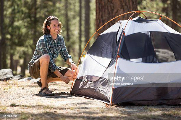 A man setting up his tent.