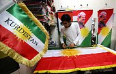 A man sews an Iraqi Kurdish flag bearing a portrait of Iraqi Kurdish leader Massud Barzani in Arbil the capital of the autonomous Kurdish region of...