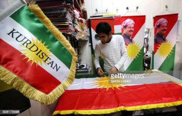 A man sews an Iraqi Kurdish flag bearing a portrait of Iraqi Kurdish leader Massud Barzani in Arbil the capital of the autonomous Kurdish region of...
