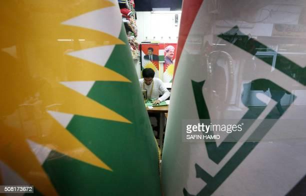 A man sews an Iraqi Kurdish flag bearing a portrait of Iraqi Kurdish leader Massud Barzani at a workshop in Arbil the capital of the autonomous...