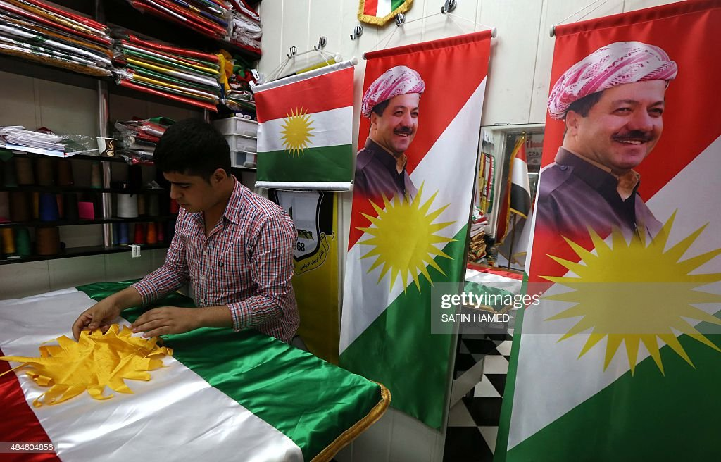 A man sews an Iraqi Kurdish flag bearing a portrait of Iraqi Kurdistan president Massud Barzani on August 20 in Arbil the capital of the autonomous...