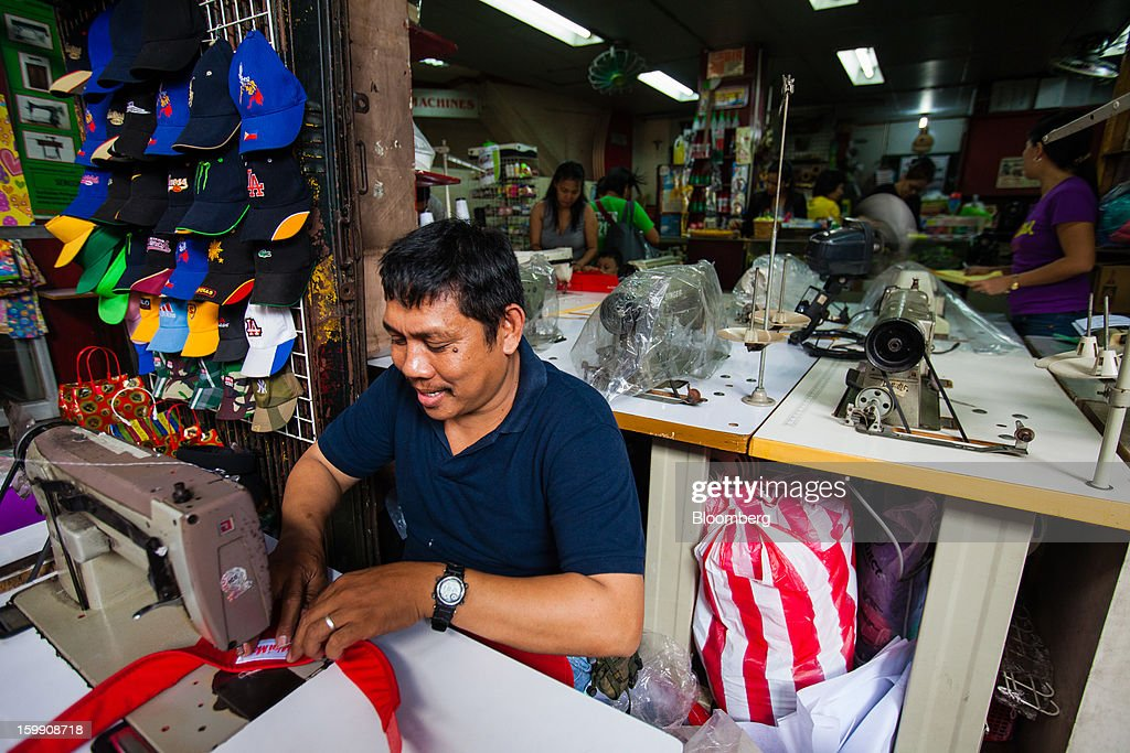 A man sews baseball caps at a sewing goods store at the Divisoria market in Manila, the Philippines, on Tuesday, Jan. 22, 2013. Philippine government bonds advanced on speculation the central bank will hold its benchmark interest rate at a record low at a meeting tomorrow, supporting demand for the nation's debt. Photographer: Julian Abram Wainwright/Bloomberg via Getty Images