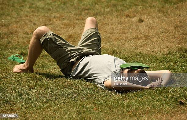 A man shades his face with one of his flipflops as he relaxes in the sun in Hyde Park on June 29 2009 in London England The Met Office has announced...