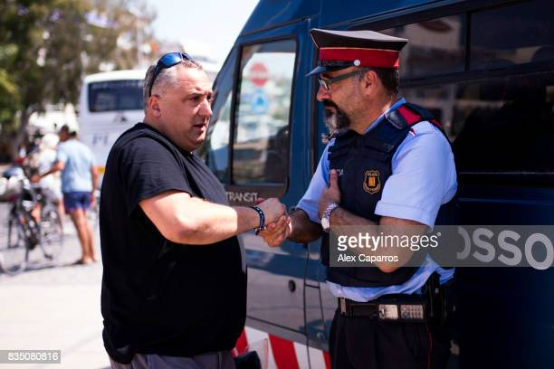 A man shakes hands with a police officer on the spot where five terrorists were shot by police on August 18 2017 in Cambrils Spain Fourteen people...