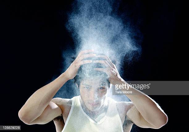 man shaking dandruff powder out of hair
