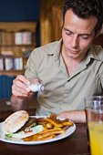 Man shaking salt on food