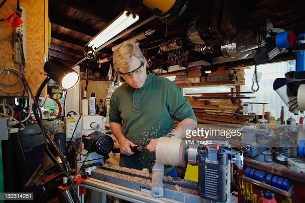 Man shaping wood on lathe