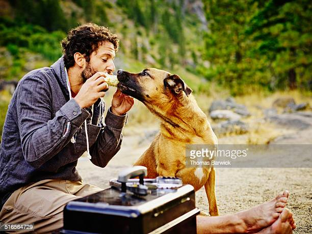 Man sharing corn on the cob with dog while camping