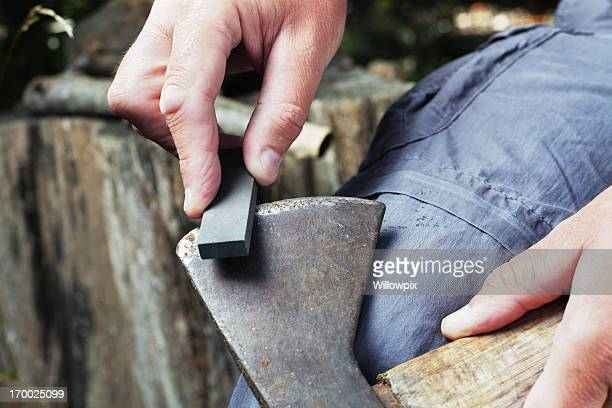 Man Sharpening Axe with Whetstone