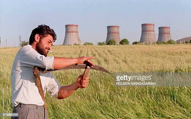 A man sharpens his scythe before cutting a field of grass next to the Armenian nuclear power station 28 kilometres from the capital Yerevan 05 June...