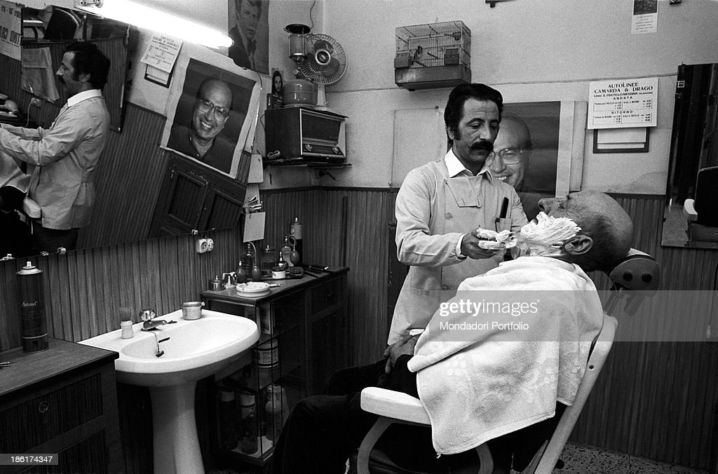 Barber In Italian : man shaved by a barber. In the shop, some posters depicting Italian ...