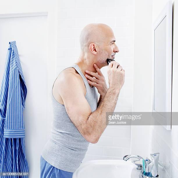 Man shaving beard at bathroom sink