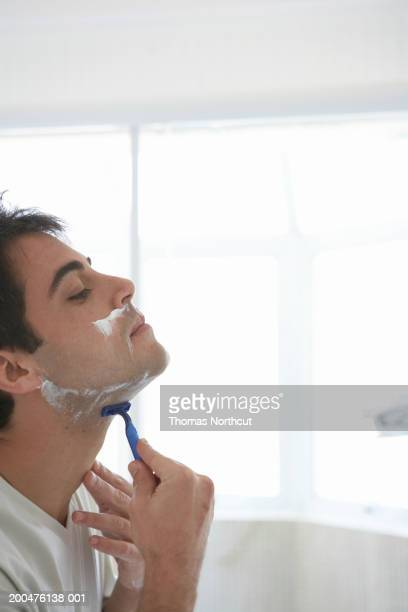 Man shaving face, head back, side view