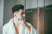 An attractive young man is seen in bathroom shaving his beard.
