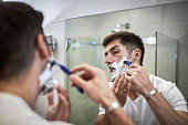 Man shaving in front of the mirror in his bathroom