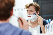 Attractive man shaving his beard in bathroom