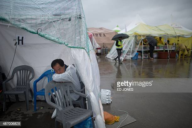A man shelters beneath a tent druing rainfall at at Jindo harbour where relatives of victims of the 'Sewol' ferry are waiting for developments in the...