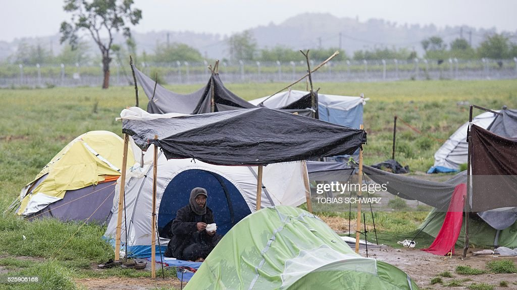 A man shelters from rain under a makeshift camp for migrants and refugees near the village of Idomeni not far from the Greek-Macedonian border on April 29, 2016. Some 54,000 people, many of them fleeing the war in Syria, have been stranded on Greek territory since the closure of the migrant route through the Balkans in February. / AFP / TOBIAS
