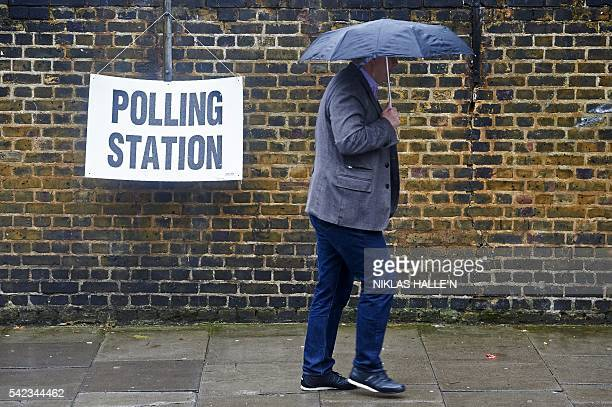 A man shelters from the rain as he arrives to vote at a polling station in London on June 23 as Britain holds a referendum on wether to stay in or to...