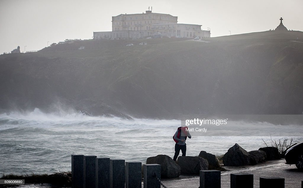 A man shelters himself from the winds in Newquay on February 8, 2016 in Newquay, England. Parts of the UK are currently being battered by Storm Imogen, the ninth named storm to hit the UK this season. Thousands of homes have been left without power and commuters hit by road and rail chaos as Storm Imogen batters the South with gale force winds and torrential rain.
