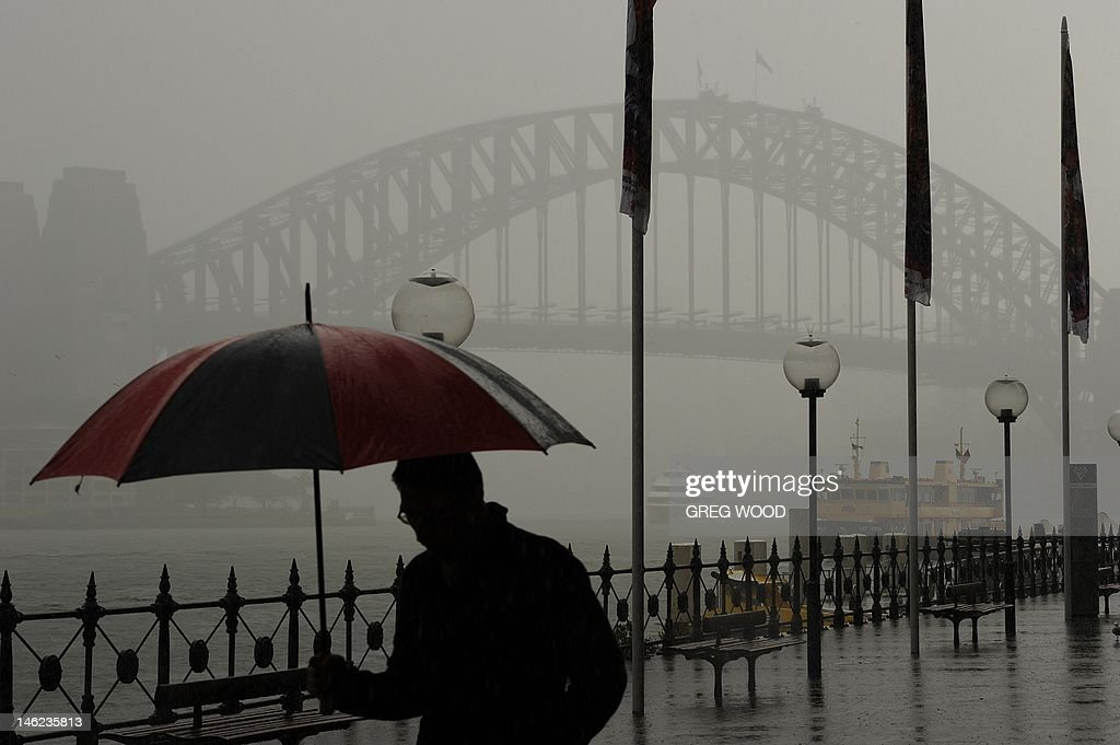 A man shelters under an umbrella as he walks along Circular Quay past the Sydney Harbour Bridge during persistent rain on June 13, 2012. Rain has been falling consistently in Sydney as winter sets in, while in Western Australia cyclone-like storms have recently wreaked havoc over a large part of the state. AFP PHOTO / Greg WOOD