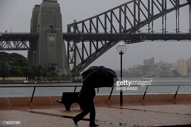A man shelters under an umbrella as storm clouds drift over the Sydney Harbour Bridge on June 15 2011 Damaging winds and heavy rain continue to...