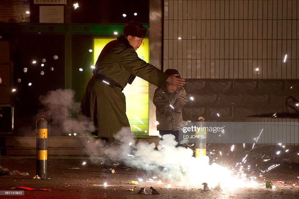 A man shields a boy from fireworks on a street in Beijing on February 9, 2013. Revellers across the city lit fireworks as China welcomed the lunar new year of the snake. AFP PHOTO / Ed Jones