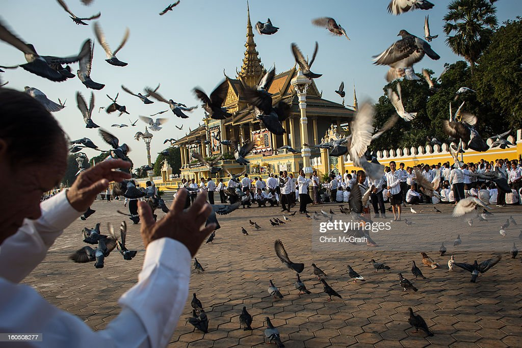 A man shields himself from flying pigeons as he waits with thousands of mourners outside the Royal Palace before being allowed to enter the cremation site to pay final respects to former King Norodom Sihanouk on February 2, 2013 in Phnom Penh, Cambodia. The former kings coffin was transported to the cremation site yesterday after being paraded through the capital in a lavish funeral procession. The cremation will take place on Monday the 4th of February, the funeral pyre will be lit by his wife and son King Norodom Sihamoni.
