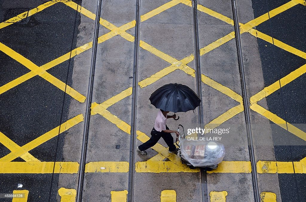 A man shields himself from the rain with an umbrella as he pushes a cart across an intersection in Hong Kong on August 13, 2014. An active southwesterly airstream associated with a trough of low pressure is bringing thundery showers to the south China coast, the Hong Kong weather observatory reported.