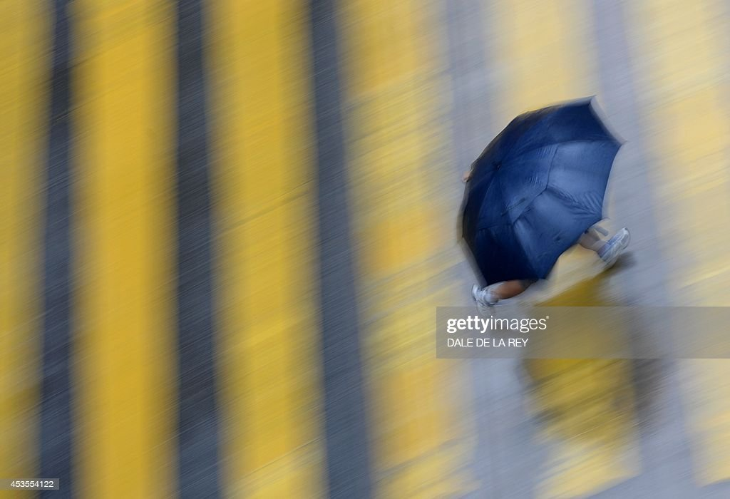 A man shields himself from the rain with an umbrella as he runs across an intersection in Hong Kong on August 13, 2014. An active southwesterly airstream associated with a trough of low pressure is bringing thundery showers to the south China coast, the Hong Kong weather observatory reported.