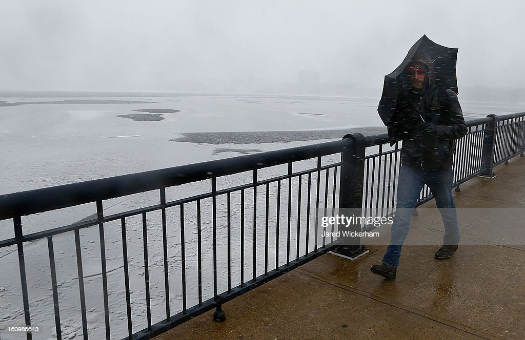 A man shields himself from the snow and wind with his umbrella while walking across the Harvard Bridge on February 9, 2013 in Boston, Massachusetts. Massachusetts and other states from New York to Maine are preparing for a major blizzard with possible record amounts of snowfall in some areas.