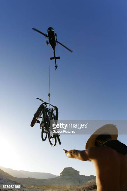 A man shields his eyes from the swirling dust after loading a bundle of mountain bikes enroute to a heli-biking adventure in Baja, Mexico.