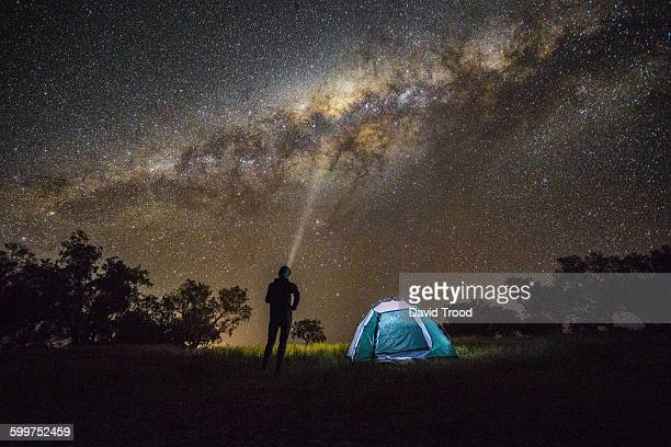 Man shining a light into the Milky Way.